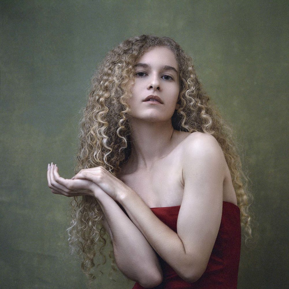 Artistic Photo Of A Blonde Girl Wearing A Red Evening Dress