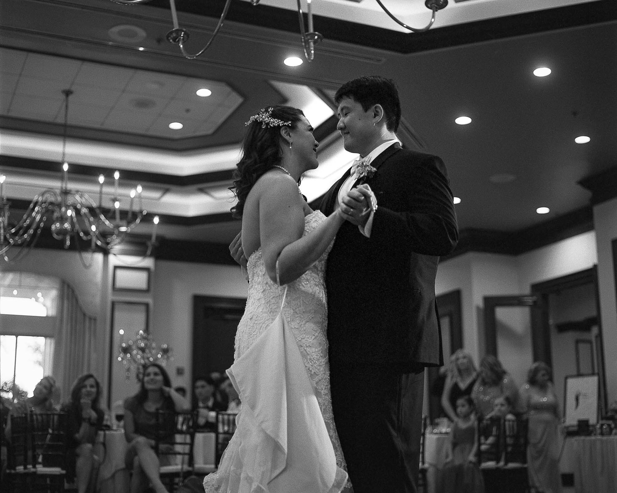 Bride and groom gazing into each others eyes during first dance at wedding reception