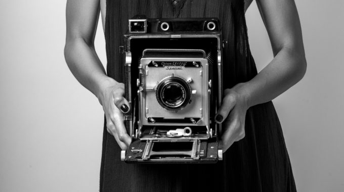 Black And White Photo Of Model Holding Large Format Camera