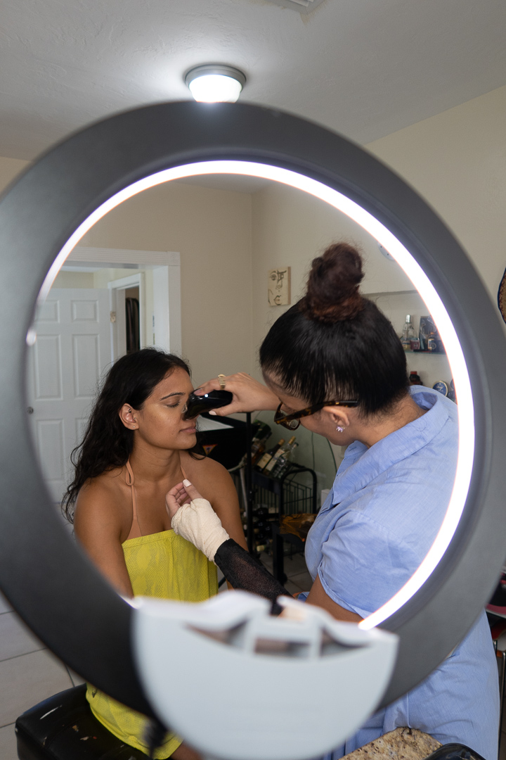 Makeup artist airbrushing client for photography session