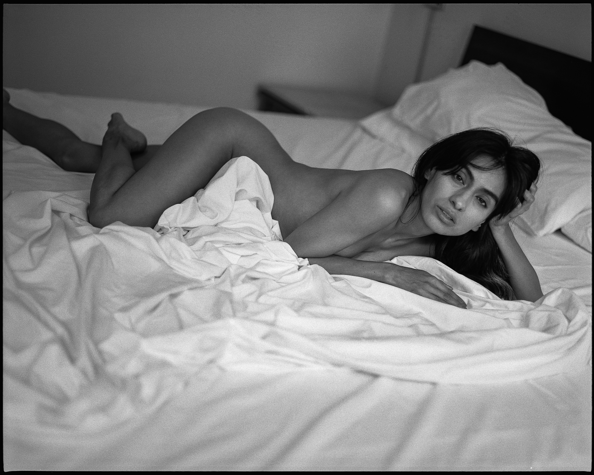naked photograph of girl laying on bed