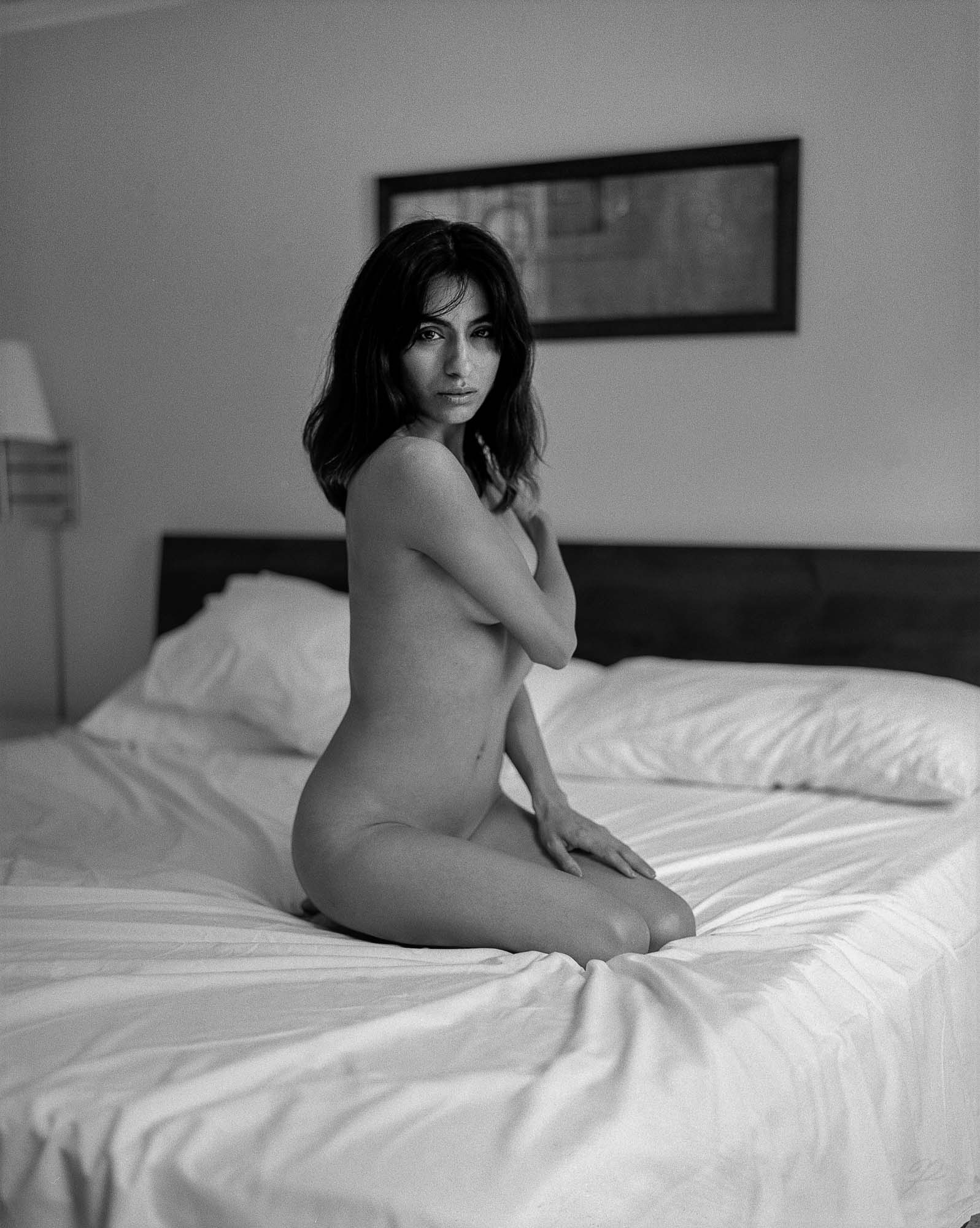 nude portrait of a lady on a bed with white sheets